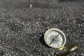 Golden Compass On Black Sand. Focus On Compass poster