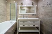 Stylish Luminous Bathroom In A Classic Style With Light Textured Walls. There Is A White Bath With G poster