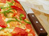 Pizza With Tomato And Green Pepper. Fresh Baked Piece Of Pizza And Knife Under The Parchment Paper. poster