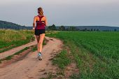 Athletic Blonde Teenage Girl Running At Dirt Road In Field. Sport Girl Running Outdoor. Young Woman  poster