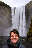 Young Male Tourist Aged 20-25 Poses In Front Of Skogafoss Waterfall In Iceland. Iceland Has Become A poster