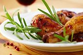 stock photo of close-up  - Roasted chicken legs with rosemary sprigs - JPG