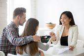 Smiling Asian Broker Giving Keys To Millennial Couple, Buying First Home Together, Female Real Estat poster