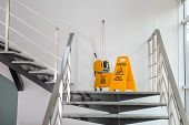Safety Sign With Phrase Caution Wet Floor And Mop Bucket On Stairs. Cleaning Service poster
