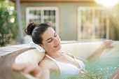 Attractive brunette woman relaxing in spa hot water poster