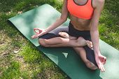 Top View Of Sporty Lady Doing Yoga On Green Grass. Lady Is Sitting In Lotus Position With Feet Cross poster