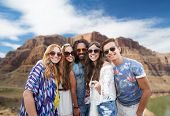 travel, tourism and technology concept - smiling young hippie friends taking picture by smartphone o poster
