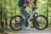 Low Angle Of Lady Wearing Sport Clothes And Sneakers While Cycling. She Is Carrying Backpack During  poster
