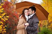 Young Couple Man And Woman Under The Umbrella, Rainy Autumn Cold Day In The Park. First Date, Love,  poster