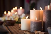 Closeup of burning candles spreading aroma on table in a spa room. Beautiful composition with grey a poster