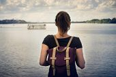 Traveler Girl Looking To River. Young Girl With Backpack Looking For A Boat. Girl Traveler Looking.  poster