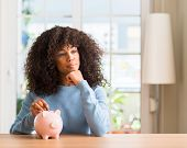 African american woman saves money in piggy bank serious face thinking about question, very confused poster