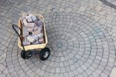 Trolley With Grey Pavers Or Bricks On A Paved Patio With Ornamental Circular Pattern Viewed High Ang poster