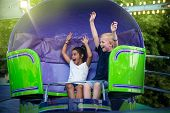 Two screaming Kids enjoying a fun summer amusement park ride. Arms raised and laughing as they twirl poster