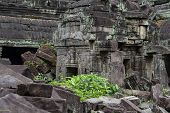 Ancient Stone Ruin In Angkor Wat Temple. Greenery In Aged Demolished Temple. Khmer Kingdom Heritage  poster