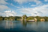 stock photo of raja  - The view of an Island with a boat leaving it Raja Ampat Indonesia  - JPG