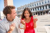 Happy couple laughing eating ice cream on vacation travel in Venice, Italy. Smiling happy young coup poster