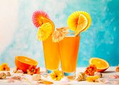 Fresh summer tropical cocktail with slice of orange,  drinking straw and cocktail umbrellas on white poster