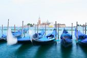 Colorful landscape with clear sky on piazza San Marco in Venice. Row of gondolas parked on city pier poster