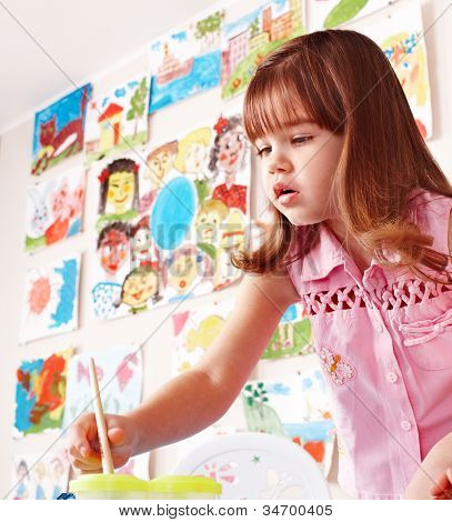 Little girl paint picture in preschool. Child care.