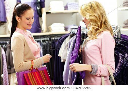 Foto de dos chicas guapas, elegir la ropa de la nueva colección de grandes almacenes