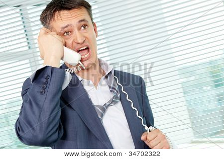 Sloppy businessman shouting into phone receiver in office