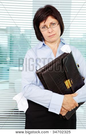 Sloppy businesswoman with briefcase looking at camera