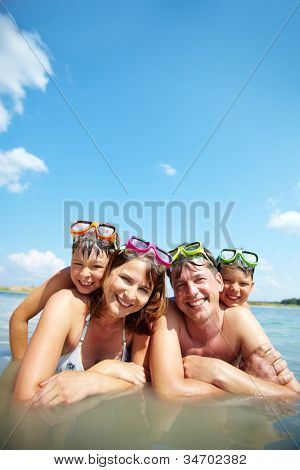 Photo of happy family looking at camera on resort