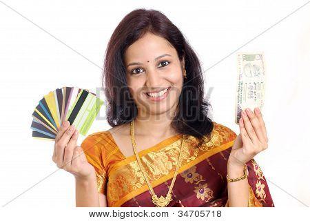 Mulher tradicional com cartões de crédito e moeda indiana