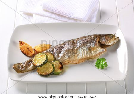 Grilled trout on a white rectangular plate with vegetables