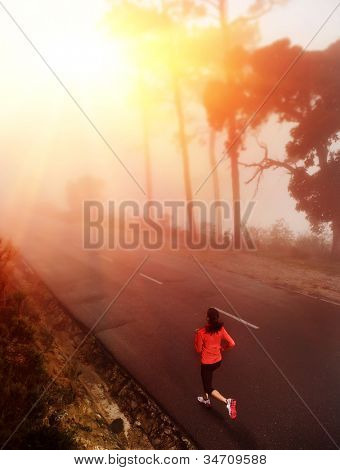 Healthy running runner woman early morning sunrise workout on misty mountain road workout jog. sun flare through the mist gives atmospheric feel and depth to this set of fitness images