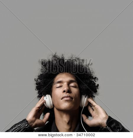 Retro man with afro listening to music on DJ headphones with eyes closed. isolated on grey background in studio.