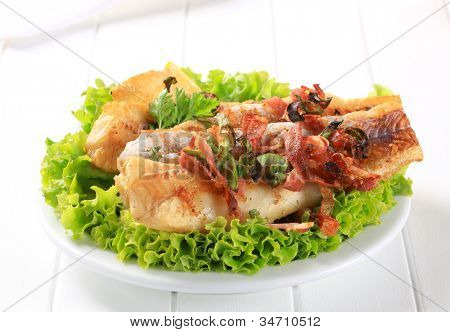 Grilled fish fillets decorated with herbs on lettuce on a white plate