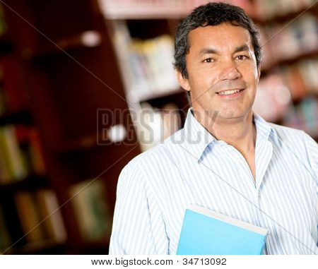 Old male university student smiling at the library