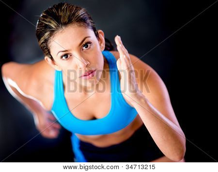 Competitive female runner over a dark background