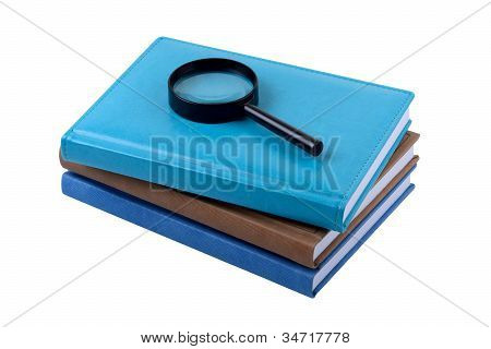 Three Books And Magnifying Lens