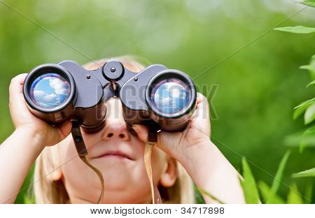 Little girl looking through binoculars outdoors