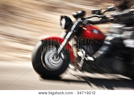 Abstract slow motion, biker riding motorbike, driver racing on the big red bike, side view, blur movement, summer road trip, speed concept