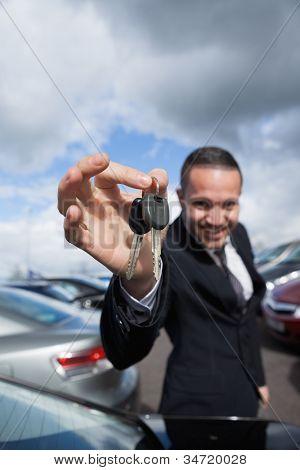 Revendedor feliz, segurando as chaves do carro, pelo seu alcance ao ar livre