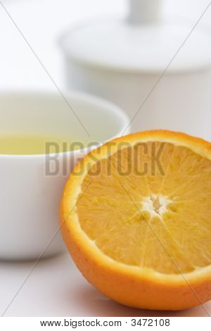 Tea Serving In White Cup With Spoon, Orange And Lime Slice In Front