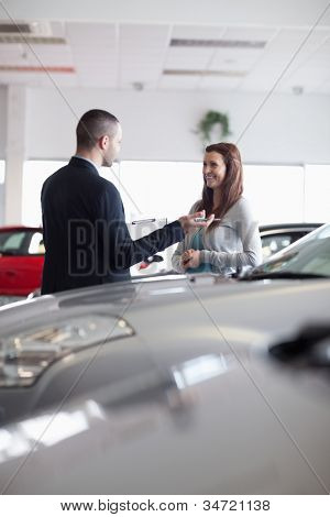 Salesman speaking with a woman in a dealership