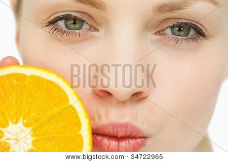 Close up of a woman placing an orange near her mouth against white background