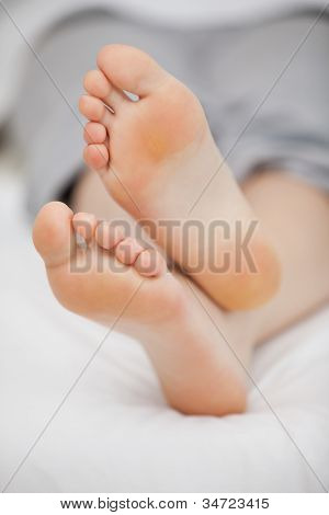 Close-up of the feet of a woman who is lying in a room