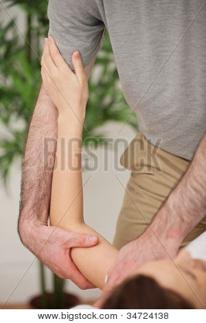 Brunette woman being manipulated by a doctor in a medical room