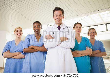 Smiling doctor and nurses with arms crossed in hospital corridor