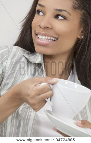 Beautiful young African American woman or girl smiling, relaxing and drinking a cup of coffee or tea