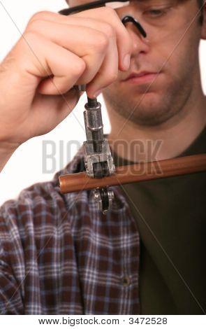 Plumber Cutting Pipe