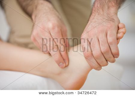 Two fingers touching and massaging a foot indoors