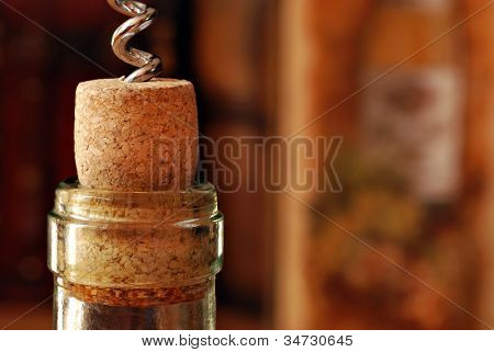 Wine bottle with corkscrew and partially removed cork.  Wine related decor in soft focus in background.  Macro with shallow dof.