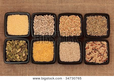 Cereal and grain selection of bulgur wheat, buckwheat, couscous, sunflower, sesame and pumpkin seed, rye grain and wild rice in black bowls on hessian sacking background.